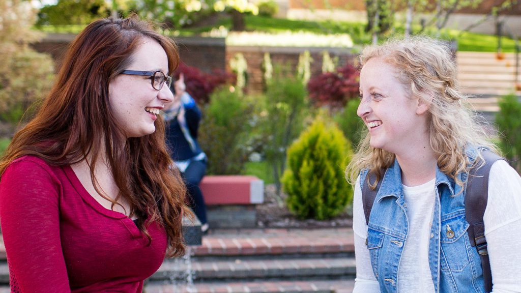 Two students chatting near the fountain between Mandelle and Dewing Hall.